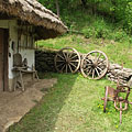 The yard of the folk house with garden tools under the eaves, as well as a plough and two cart wheels - Komlóska, Maďarsko