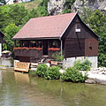 """Waterfront old guesthouse in the Rastoke """"mill town"""", in the background a rock wall can be seen, on the other side of the Korana River - Slunj, Croacia"""