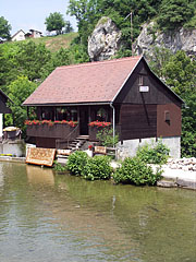 """Waterfront old guesthouse in the Rastoke """"mill town"""", in the background a rock wall can be seen, on the other side of the Korana River - Slunj, Hrvaška"""