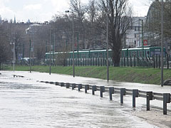 """Flood on the lower embankment, with a green """"HÉV"""" suburban train in the background - Budapeszt, Węgry"""