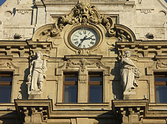 """Symbolical female figures of the """"Thrift"""" (or """"Thriftiness"""") and the """"Richness"""" (or """"Plenty"""") on the main facade of the New York Palace, with a clock between them - Budapest, Ungarn"""