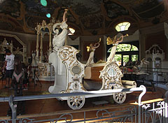 One of the white carriages in the old carousel (merry-go-round), with trumpeting angel or fairy statues - Budapest, Ungarn