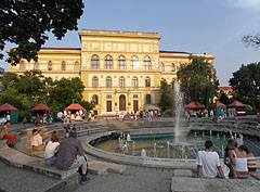 The surroundings of the great music fountain is a famous relaxing and meeting place, and behind it the yellow main building of the University of Szeged is bathing in the sunlight  - Szeged (Szegedin, Segedin), Ungarn