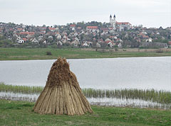 """Bundles of reeds in front of the Inner Lake (""""Belső-tó""""), and behind it in the distance there are the houses of the village, as well as the double towers of the Benedictine Abbey Church - Tihany, Ungarn"""