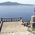 """View to the Adriatic Sea and the Lopud Island (""""Otok Lopud"""") from the stairs of the rocky hillside; in the foreground there is a spacious stone terrace with a statue of St. Balise beside it - Trsteno, Kroatien"""