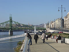 Pleasant late-autumn sunshine on the promenade on the Danube bank (and the green colored Liberty Bridge in the background) - Boedapest, Hongarije