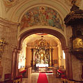 Looking towards the sanctuary: upwards a splendid fresco, on the right the carved wooden pulpit can be seen - Gödöllő, Hongarije
