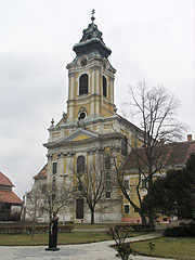 The Assumtion of Virgin Mary Church on the main square, as well as the half-length statue of Kálmán Széll Hungarian parliamentarian and prime minister (1843-1915) in front of it - Szentgotthárd, Hongarije