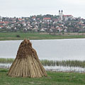 """Bundles of reeds in front of the Inner Lake (""""Belső-tó""""), and behind it in the distance there are the houses of the village, as well as the double towers of the Benedictine Abbey Church - Tihany, Hongarije"""