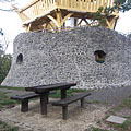 The stone-made lowest level of the Várhegy Lookout Tower, in front of it there are wooden benches and a table - Fonyód, Ungarn