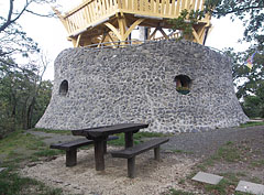 The stone-made lowest level of the Várhegy Lookout Tower, in front of it there are wooden benches and a table - Fonyód, هنغاريا