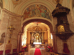 Looking towards the sanctuary: upwards a splendid fresco, on the right the carved wooden pulpit can be seen - Gödöllő, هنغاريا
