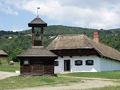 A small wooden belfry from Felsőszenterzsébet, and the house from Baglad is behind it - Szentendre, هنغاريا