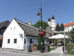 The Csárdás Restaurant in the farmhouse with porch, and some distance away there are the white steeples (towers) of the Benedictine Abbey of Tihany - Tihany, هنغاريا