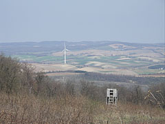 A wooden hunting high-stand in the hillside at the Galamb-berek (grove), as well as a wind turbine in the valley (near Szápár settlement) - Bakony Mountains, Hungary