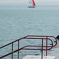 One of the stairs of the beach, as well as in the distance a sailboat can be seen - Balatonfüred, Hungary