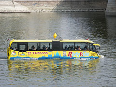 A yellow amphibious bus and tourist boat in one is swimming on the Danube River - Budapest, Hungary