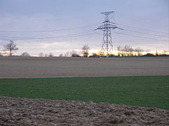 Plowed field with a transmission tower or electricity pylon at sunset - Eplény, Hungary