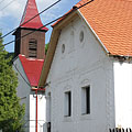 The St. Anne's Church of Háromhuta with its wooden steeple (tower), and an old welling house next to it - Háromhuta, Hungary