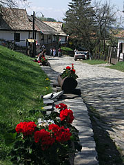 A street paved with natural stone, decorated with geranium flowers - Hollókő, Hungary