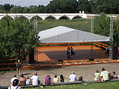 Folk dance program on the stage of the open-air theater, and the Nine-holed Bridge in the background - Hortobágy, Hungary