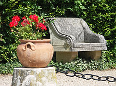 Stone bench and a vase with geranium flowers in the garden of the Széchenyi Mansion of Nagycenk - Nagycenk, Hungary