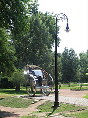 "The metal sculpture called ""Homecoming - Gyula Krúdy"" and a lamp post at the edge of a park - Nyíregyháza, Hungary"