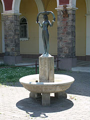 """Girl with fish"" statue in an ornamental fountain in front of the thermal bath archway - Szolnok, Hungary"