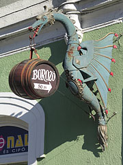 The green dragon figure on the wall, that holds a barrel on its tongue is actually the sign of a wine bar by the lake - Tapolca, Hungary
