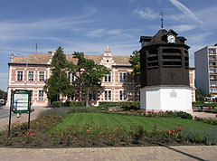 The Clock Tower in the small flowered park, and the Vaszary János Primary School is behind it - Tata, Hungary
