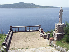 "View to the Adriatic Sea and the Lopud Island (""Otok Lopud"") from the stairs of the rocky hillside; in the foreground there is a spacious stone terrace with a statue of St. Balise beside it - Trsteno, Croatia"